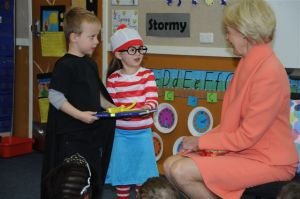 Kindergarten students Daniel Harmer and Ava Singer present the Governor-General with a specially bound book of handwritten notes.